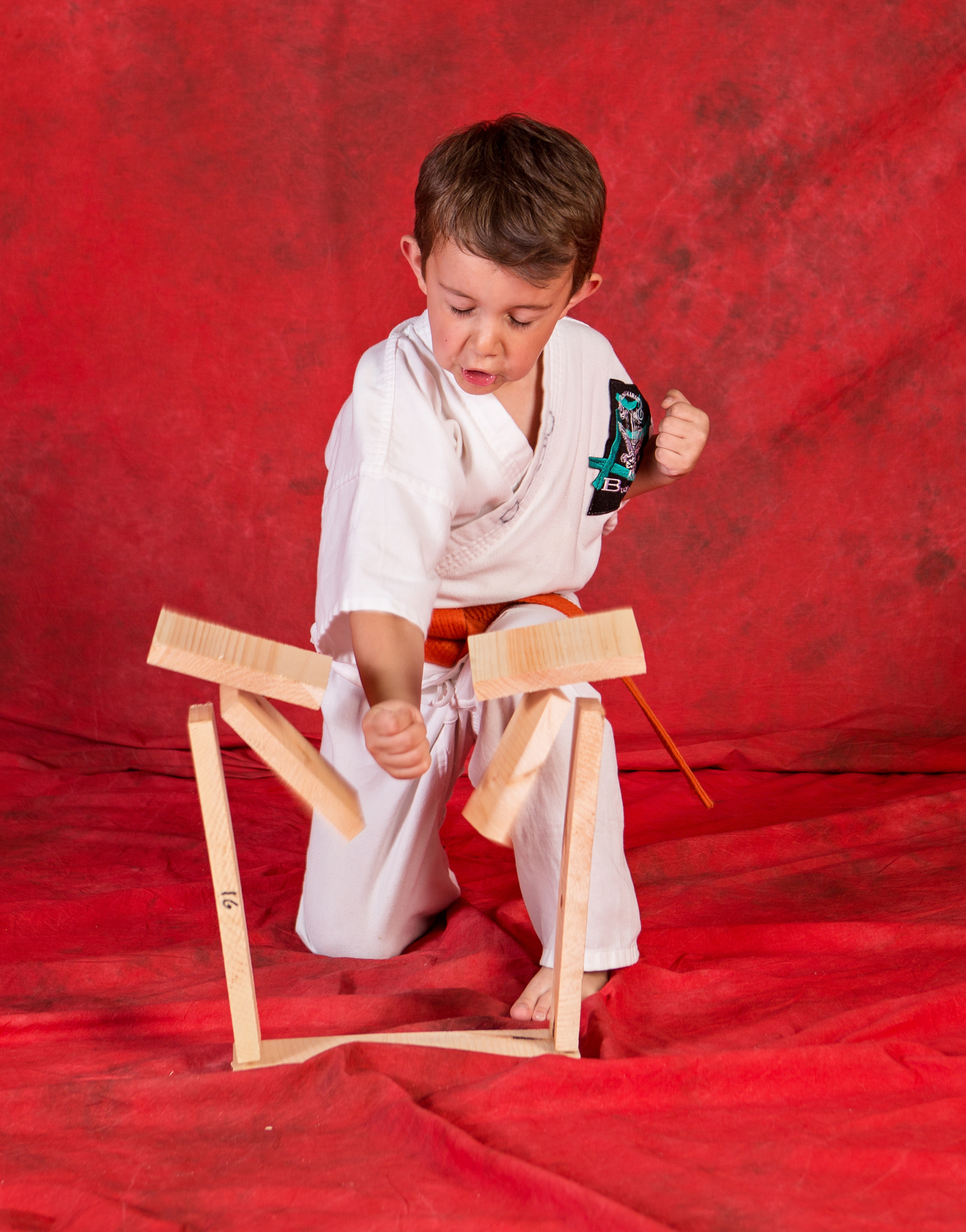 young karate student breaks wodd boards
